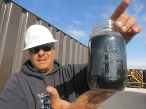 "PHOTO BY MOSE BUCHELE The new black gold? Brian Schoonover works for Water Rescue Services, a group that treats brackish and ""produced"" water so it can be used in hydraulic fracturing. Here he holds a mason jar of produced water, ready for treatment."